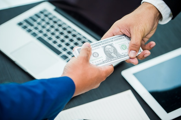 Business hand giving money workspace in office- united states dollars (or usd)