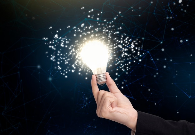 Business hand holding light bulb, concept of new ideas with innovation and creativity.