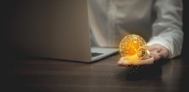 Business hand holding light bulb, creativity and innovation are keys to success