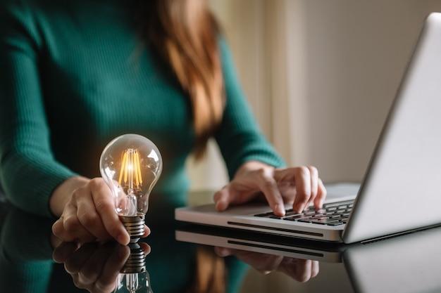 ラップトップコンピューターとオフィスでお金のスタックを使用して電球を持っているビジネスの手。朝の光の中でエネルギーと会計ファイナンスの概念を節約するアイデア