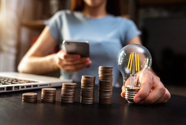 비즈니스 손을 사무실에서 랩톱 컴퓨터와 돈 스택을 사용 하여 전구를 잡고. 아이디어 절약 에너지 및 회계 금융 개념