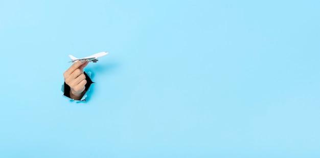 비즈니스 손 파란색 배경에 벽에 구멍에서 모델 평면을 보유하고있다. 보험 여행 개념. 파노라마 이미지