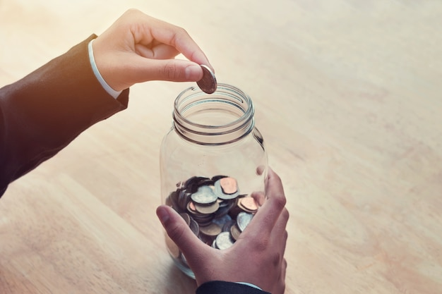 Business hand putting coins in glass jar for saving money accounting concept on table