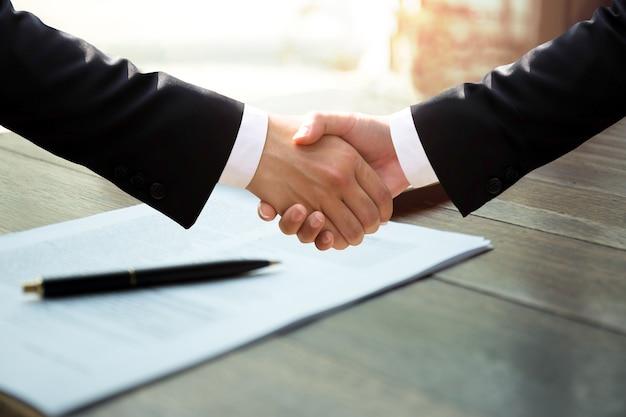 成功した契約に署名した後の紙の仕事の上のビジネスハンドシェイク