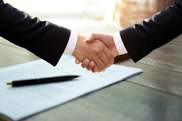 Business hand shake over paper work after signing a contract successful