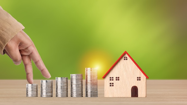Business hand walking on stacking coins saving growth on wooden desk with model house on green background