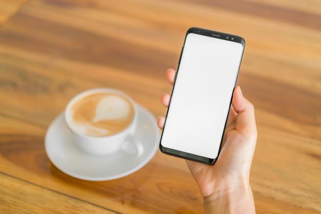 携帯電話とラテアートコーヒーを持つビジネスハンド。