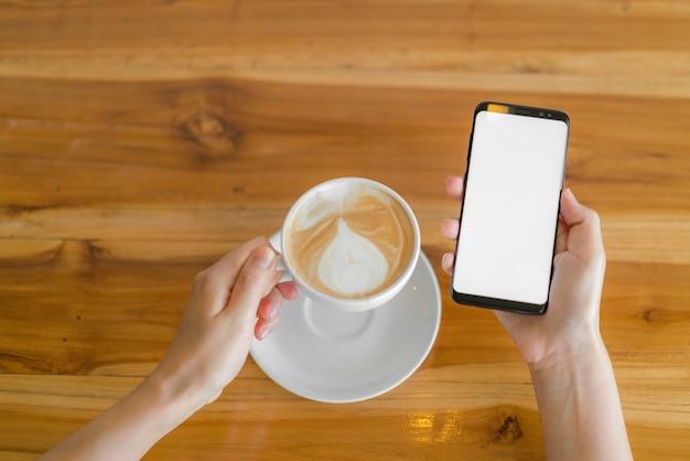 Mano d'affari con il telefono cellulare e il latte art coffee.