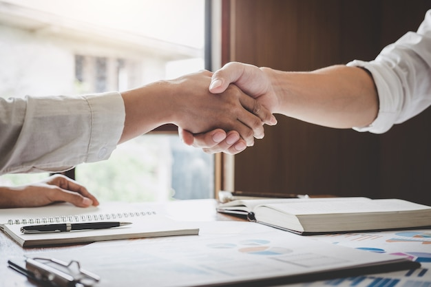 Business handshake after discussing good deal of trading to sign agreement