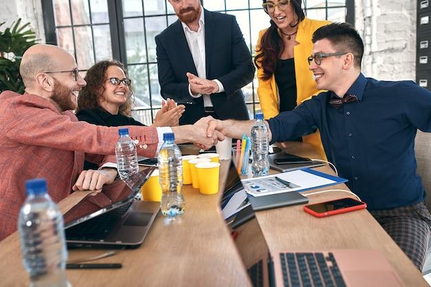 オフィスでの会議や交渉でのビジネスハンドシェイク。契約書や財務書類に署名することで、パートナーは満足しています。セレクティブフォーカス。