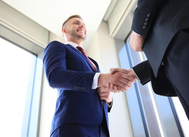 ビジネスハンドシェイク。取引を成立させるために握手を与えるビジネスマン