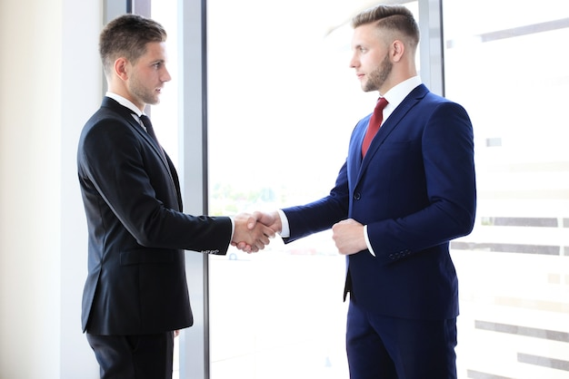 Business handshake. business man giving a handshake to close the deal Premium Photo