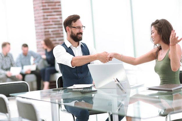 Business handshake of a businessman and businesswoman .
