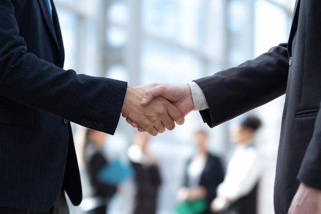 オフィスの背景にビジネス握手クローズアップ。