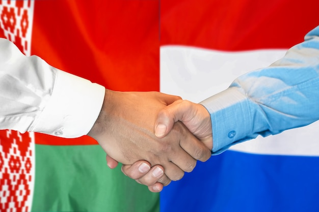 Деловое рукопожатие на фоне двух флагов.