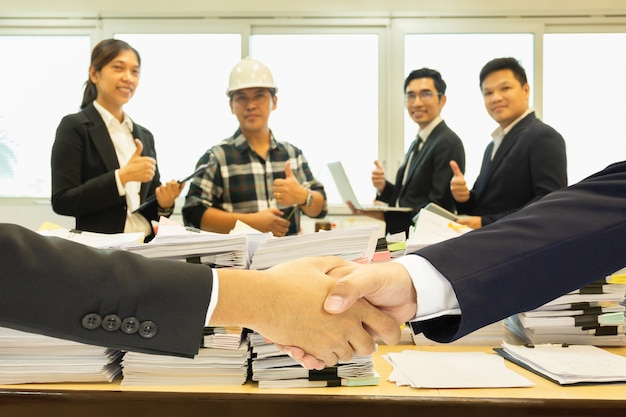 Business handshake successful with pile of paperwork and group of teamwork in background.