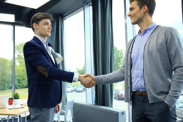 비즈니스 악수입니다. 사무실에서 악수 하는 두 사업가.