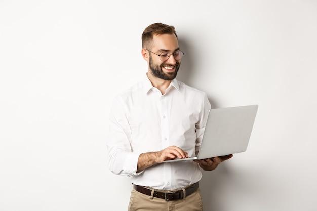 사업. 노트북에서 일하고 메시지에 응답하고 웃고, 서있는 잘 생긴 사업가