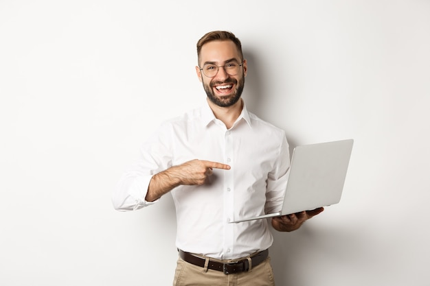 Business. handsome manager in glasses working on laptop, pointing at computer and smiling pleased, standing