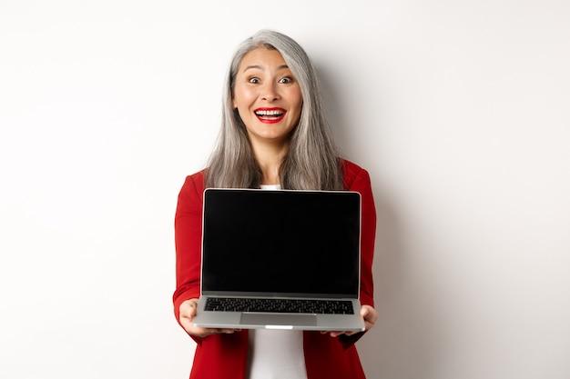 Бизнес. счастливая старшая женщина-предприниматель демонстрирует пустой экран ноутбука, изумленно улыбаясь в камеру, стоя на белом фоне