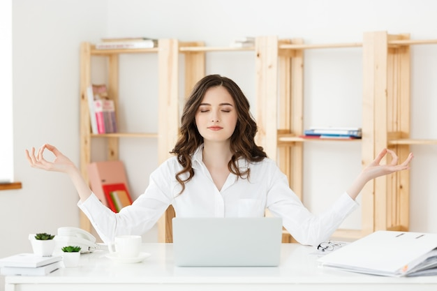 Business and health concept portrait young woman near the laptop practicing meditation at the office desk in front of laptop online yoga classes taking a break time for a minute