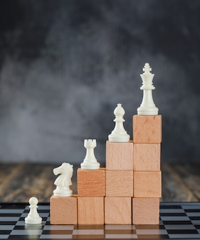 Business hierarchy concept with chessboard, figures, pyramid of wooden blocks on foggy and wooden table side view.