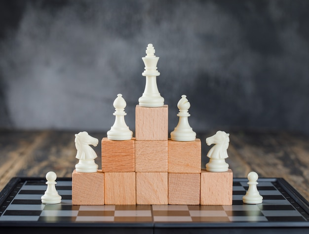 Business hierarchy concept with chessboard, figures on pyramid of wooden blocks on foggy and wooden table side view.