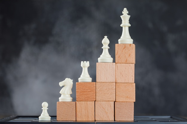 Business hierarchy concept with figures on pyramid of wooden blocks on foggy and chessboard side view.