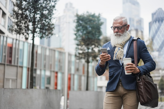 Business hipster senior man using mobile phone while walking to work with city in background - focus face