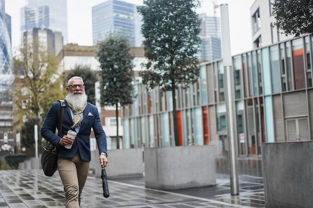 백그라운드에서 도시와 함께 일하기 위해 걷는 비즈니스 힙스터 시니어 남자 - 초점 얼굴