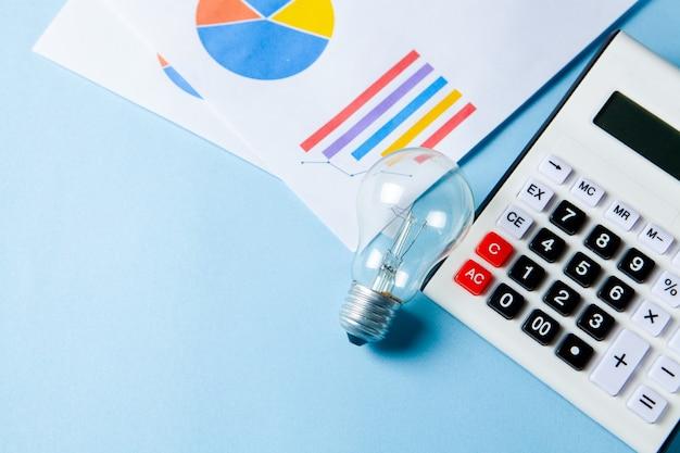 ビジネスアイデアの概念。電卓の横にあるコインと青い表面のテーブルのランプ