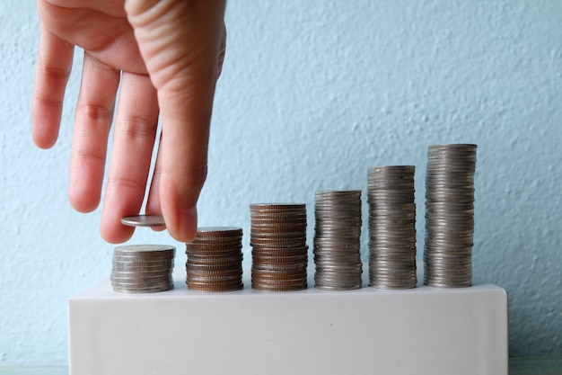 Business idea concept , hand put coin stacking to money