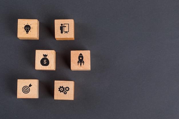 Бизнес-идея концепции с иконками на деревянных кубиков на темно-серый стол плоской планировки.