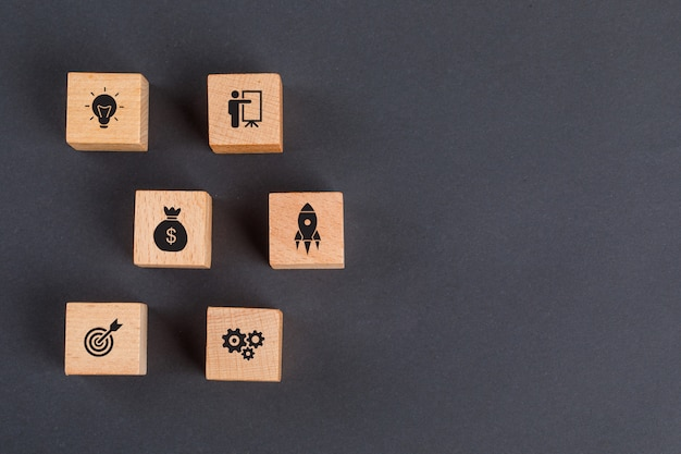 Business idea concept with icons on wooden cubes on dark grey table flat lay.