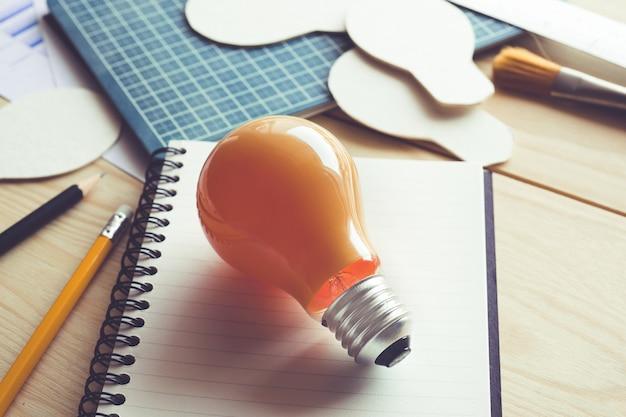 机のテーブルに電球を置いたビジネスアイデア。
