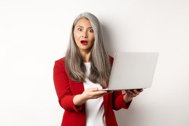 Бизнес. впечатленная азиатская старуха, работающая на ноутбуке, глядя в камеру, удивлена, стоя на белом фоне