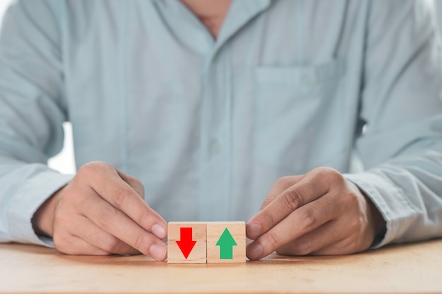 Business increasing or decreasing , businessman holding green up arrow or red down arrow which print screen on wooden cube block.