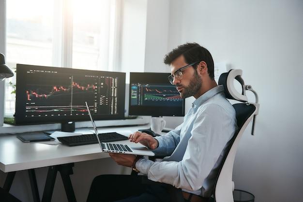 Деловая информация бородатый трейдер в очках анализирует финансовый рынок через ноутбук, пока