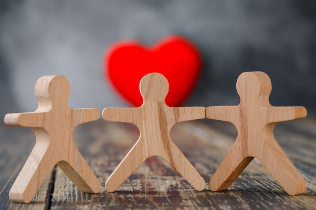 Business and insurance concept with wooden figures of people, red heart close-up.