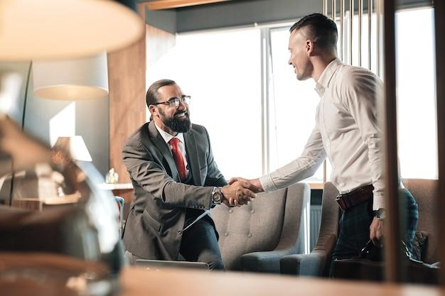 ビジネス面接。ビジネス面接に来ている間興奮している白いシャツを着ている若いハンサムな男