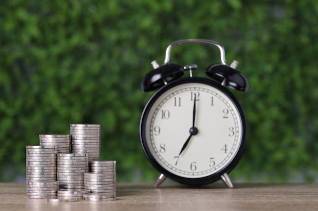 광고 개념을 위한 비즈니스 투자 및 저축 성장. 나무 탁자에 시계와 함께 자라는 동전 쌓기, 녹색 자연 배경, 세금 또는 돈 벌기의 의미