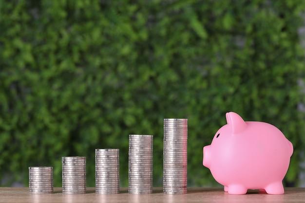 広告コンセプトの事業投資と成長の節約。緑の自然の背景にピンクの貯金箱で成長するコインを積み重ねる、成長するか、節約するか、お金を稼ぐことを意味します