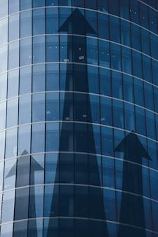 Концепция роста инвестиций в бизнес с абстрактными стрелками на здании.