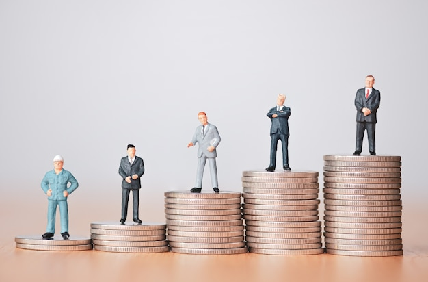 Business investment and planing concept. businessman miniature figure standing on coins stacking.