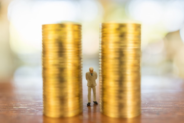 Business, investment and planning concept.  close up of  businessman miniature people figure standing between stack of gold coins on wooden table.