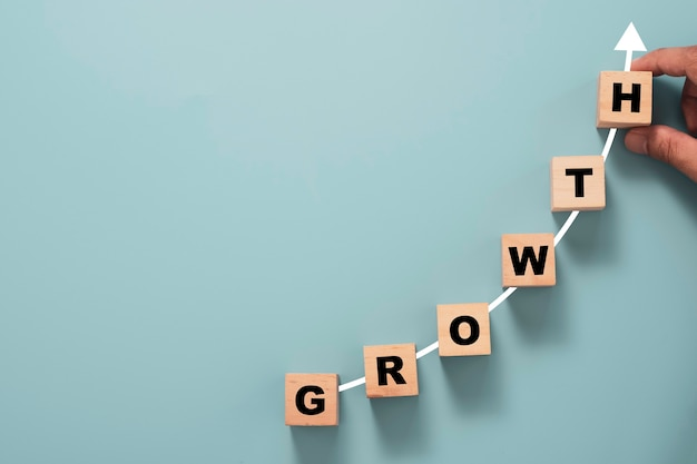 Business investment and profit growth concept, hand putting growth wording with increasing arrow on blue background.