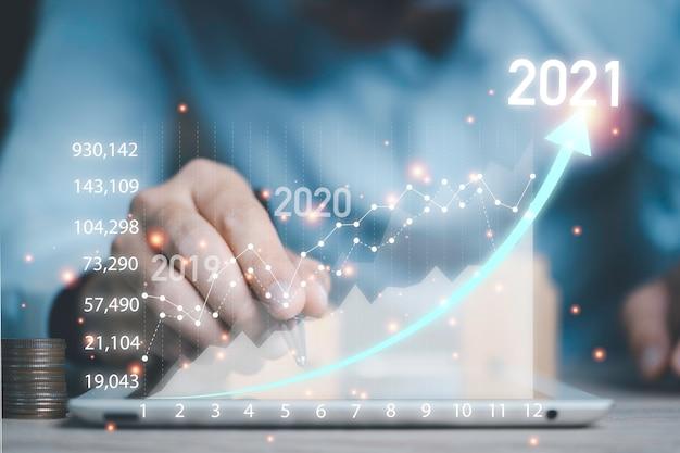 모바일 태블릿을 사용하여 아름다운 가상 주식 시장 차트를 분석하는 비즈니스 투자자
