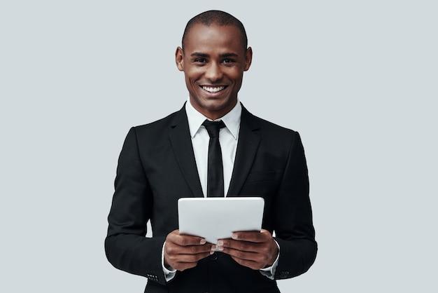 사업은 그의 삶이다. 회색 배경에 서 있는 동안 디지털 태블릿을 사용하여 작업하는 정장 차림의 매력적인 젊은 아프리카 남자