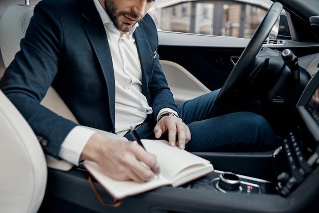 사업은 그의 삶이다. 차 안에 앉아있는 동안 개인 주최자에 뭔가를 적는 완전한 정장을 입은 젊은 남자의 클로즈업