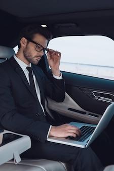 사업은 그의 삶입니다. 노트북을 사용하고 차에 앉아있는 동안 그의 안경을 조정하는 전체 소송에서 사려 깊은 젊은 남자